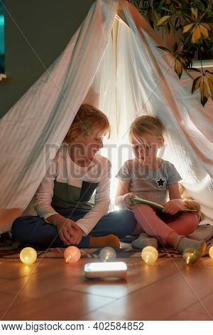 Two Little Kids, Boy And Girl Reading A Book Together While Sitting On A Blanket In A Hut Made With