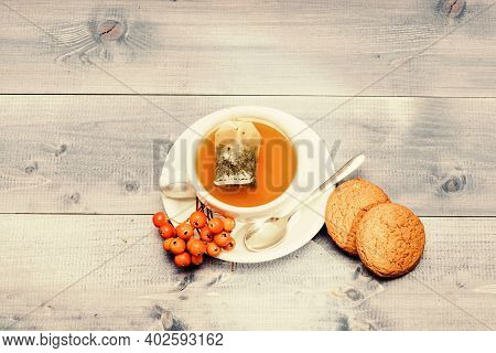Health Care Folk Remedies. Drink Aromatic Rowanberry Beverage. Cup Of Tea On Blue Background Close U