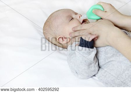 A Mother Uses A Nasal Aspirator On A Sick Baby, Sucking Mucus From The Nose. Copy Space - The Concep