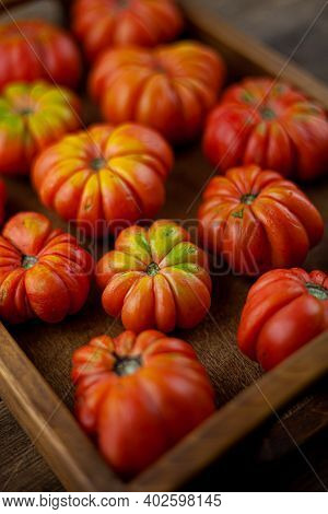 Red Ribbed Tomatoes On A Wooden Background. American Or Florentine Variety Nina . Tomato Top View. F