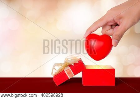 Valentine Day, Hand Put Heart Shape In Red Gift Box On Wooden Bokeh Background, Celebration And Anni