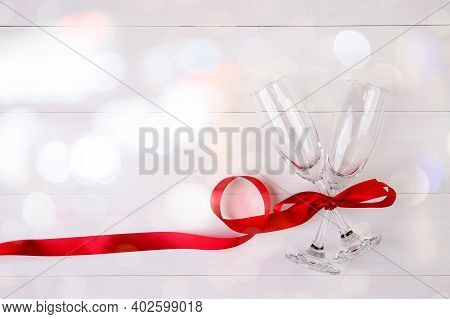 Valentine Day Concept, Wineglass And Red Ribbon On White Wooden Table Background With Bokeh, Champai