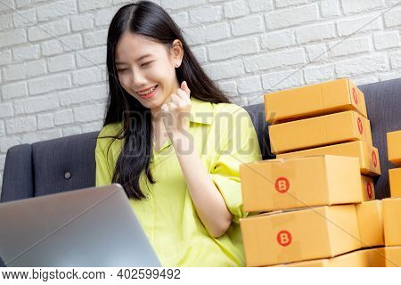 Young Asian Woman Is Merchant Using Laptop Computer On Sofa Checking Order Of Customer With Purchase