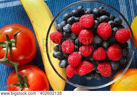Fruits mix insige glass bowl and tomato on table top view