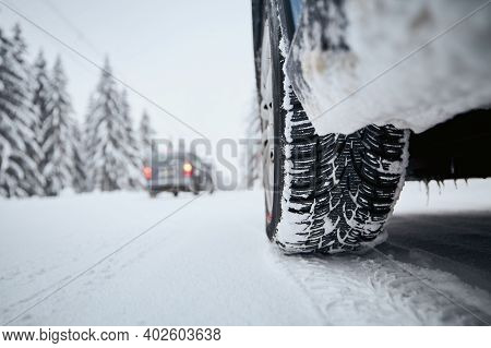 Close-up View Of Tire Of Car On Snow Covered And Icy Road. Themes Safety And Driving In Winter.