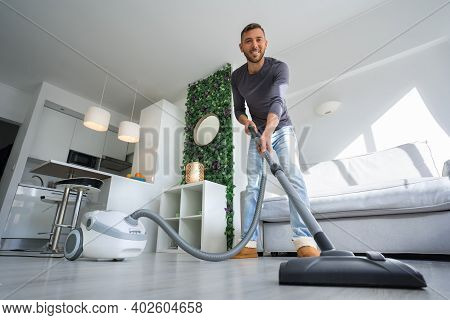 Young Attractive Man Using A Vacuum Cleaner At Home. Man Cleaning House. House Keeping Concept
