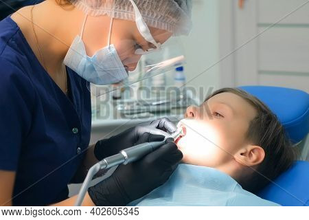 Dentist Hygienist Making Oral Hygienic Cleaning In Dentistry For Teen Child Boy. Using Professional