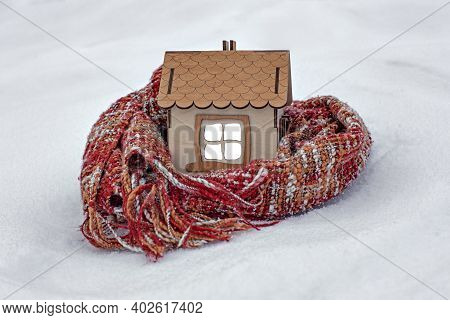 A Wooden House In The Snow In Winter, A Knitted Scarf Around The House, The Concept Of Insulation An
