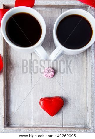 Two coffee cups and sweets making funny face on the wooden tray