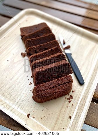 Homemade Dark Bitter Chocolate Moist Sponge Cake Slices Slices In Tray With Knife.