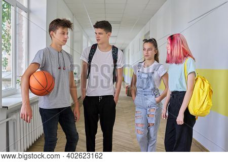 A Group Of Teenage Students 16 Years Old In The School Hallway. Walking Talking Teenagers With Backp