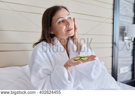 Face Skin Care Of Middle Aged Woman. Mature Female In Bathrobe Doing Home Spa Treatments With Cucumb