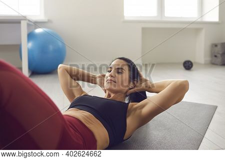 Fit Woman Doing Crunches Or Sit-ups On Gym Mat During Routine Sports Workout At Home