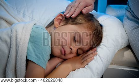 Closeup Of Young Mother Stroking And Caressing Her Little Son Sleeping In Bed At Night. Loving And C
