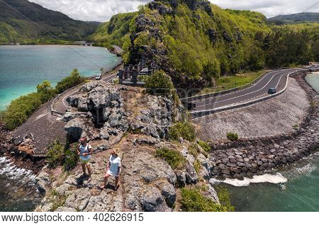 The Couple Stands On The Edge Of A Cliff On The Island Of Mauritius.an Unusual Road To The Islands O