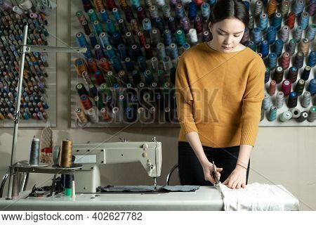 A Caucasian Dressmaker Stands At A Work Table And Cuts White Fabric Along A Pattern With Scissors. T