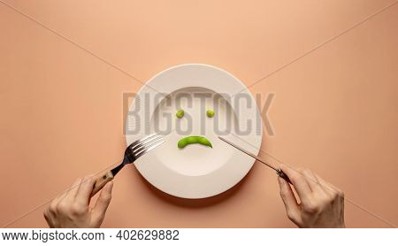 Diet Or Anorexic In Health Care Concept. Eating Disorder. Lose Weight. Young Woman Using Fork And Kn
