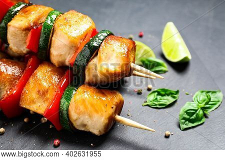 Delicious Chicken Shish Kebabs With Vegetables On Black Table, Closeup