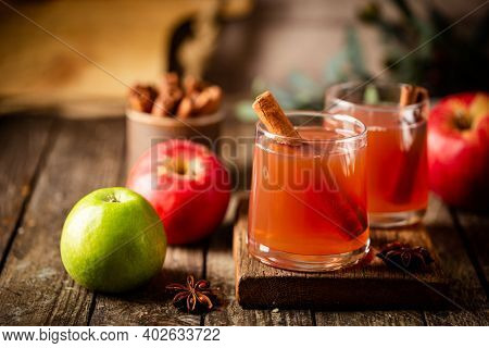 Glass Of Fresh Apple Juice With Cinnamon And Red Apples On Wooden Background