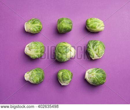 Fresh Brussels Sprouts On Purple Background, Flat Lay