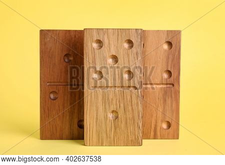 Wooden Domino Tiles With Pips On Yellow Background