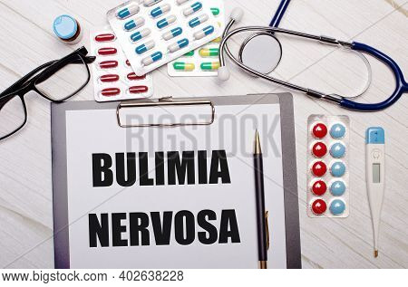 On A Light Wooden Background There Is Paper With The Inscription Bulimia Nervosa, A Stethoscope, Col