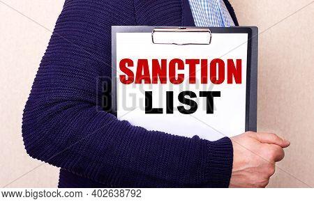 Sanction List Is Written On A White Sheet Held By A Man Standing Sideways