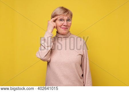 Senior Woman Pointing Finger Up And Looking Inspired By Genius Thought, Showing Good Idea Sign, Havi
