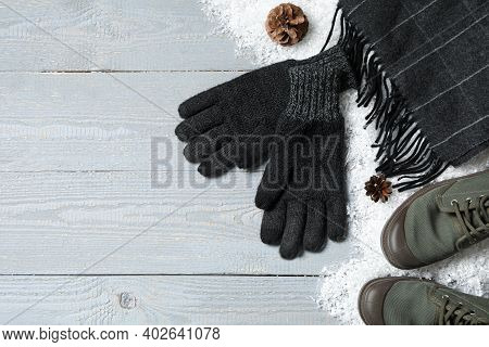 Stylish Woolen Gloves, Scarf, Pair Of Shoes And Winter Decor On Grey Wooden Table, Flat Lay. Space F