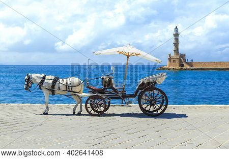 Horse Drawn Carriages On The Quayside With The Venetian Lighthouse At The Harbour Entrance To The Re