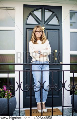 Full Length Of Confident Mature Woman Standing With Arms Crossed At The Front Door In Her Home.