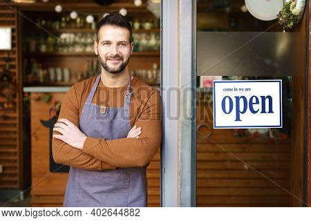 Portrait Of Smiling Owner Man Standing At His Cafe Door With Open Signboard.