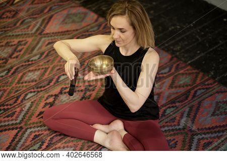Woman Playing On Tibetan Singing Bowl While Sitting On Yoga Mat. Vintage Tonned.