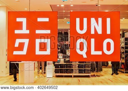 Glowing Sign With Brand And Logo Of Uniqlo Clothing Store On Glass Showcase In Shopping Center. Uniq