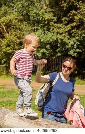 Family On Walk In Park. Mom Helps Baby To Keep Balance On Balance Beam. The Child Is Happy And Delig