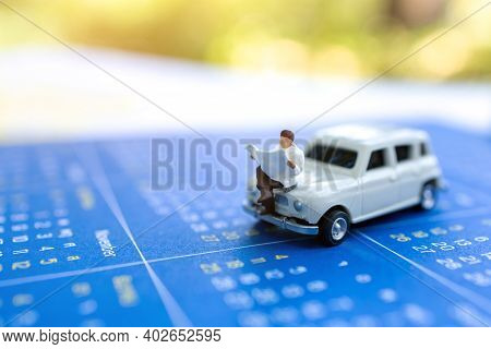 Miniature People: Businessman Reading On Car And Calendar, Education Or Business Concept.