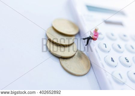 Miniature People: Businessman Reading A Book With Coins And Sitting On The Calculator And Calendar.