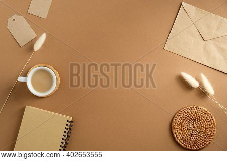 Elegant Feminine Workspace With Cup Of Coffee, Paper Envelope, Notebook, Dry Flowers On Brown Backgr