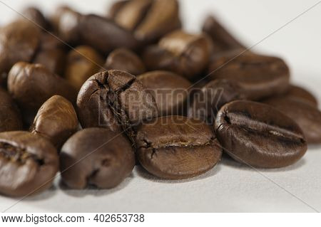 Grains Of Black Aromatic Coffee Close-up. Brown Roasted Coffee Beans Background On White. Espresso I