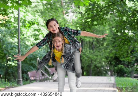 Happy Childhood Friends Have Fun Piggybacking In Park On Summer Day, Holidays.