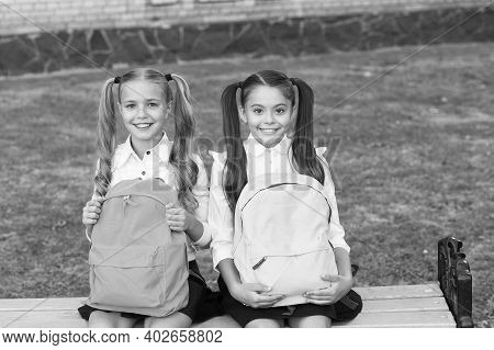 Study Together To Accomplish More. Happy Girls Study In Primary School. Little Children Hold Bags Ou