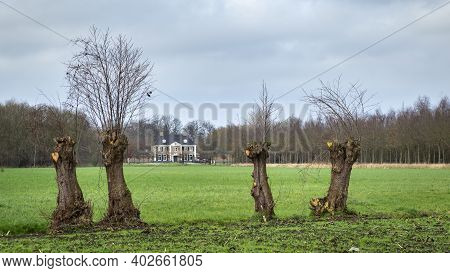 Ederveen, Netherlands - December, 12, 2020: Typical Dutch Mansion Between Willows At The Countryside