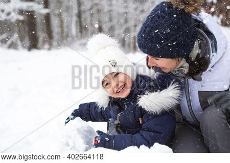 Mom And Daughter Play Snow Games, Build A Fortress, Make Snowballs. Winter Entertainment Outside, Ac