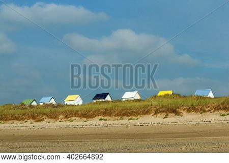 The Tiny White Beach Cottages With Colorful Roofs At A Beach By Gouville-sur-mer In France In Norman