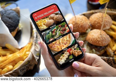 Female Hands Hold Phone With Food Delivery Application On Screen Against Background Of Burgers And F