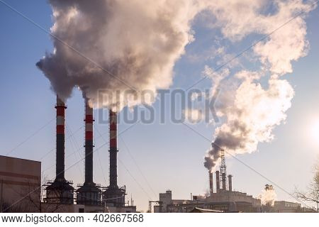 Factory Pipes With Smoke On Blue Sky Background. Industrial Smokestacks Sending Thick Smoke To Blue