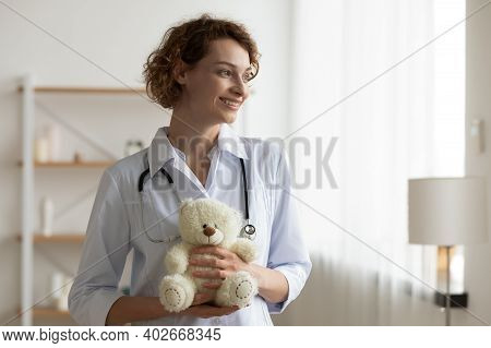 Smiling Young Kind Female Pediatrician Holding Teddy Bear In Hands.