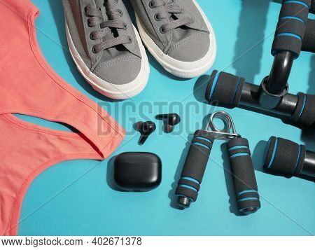 Flat Lay Of Sport And Fitness Equipment On Blue Background. Pantone Stay Home Training And Workout C