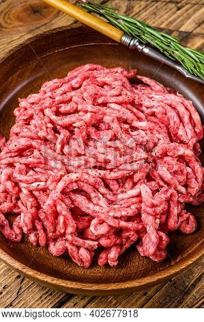 Raw Mince Lamb, Ground Mutton Meat With Herbs On A Plate. Wooden Background. Top View