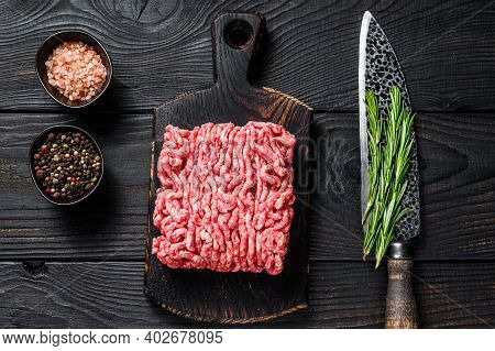 Raw Mince Lamb, Ground Meat With Herbs And On A Wooden Cutting Board. Black Wooden Background. Top V